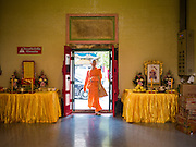 28 AUGUST 2015 - BANGKOK, THAILAND: A Mahayana Buddhist monk walks into Wat Mangkon Kamalawat in the Chinatown section of Bangkok. Wat Mangkon Kamalawat is the largest Mahayana Buddhist temple in Chinatown. Mahayana  Buddhists believe that the gates of hell are opened on the full moon of the seventh lunar month of the Chinese calendar, and the spirits of hungry ghosts allowed to roam the earth. These ghosts need food and merit to find their way back to their own. People help by offering food, paper money, candles and flowers, making merit of their own in the process. Hungry Ghost Day is observed in communities with a large ethnic Chinese population, like Bangkok's Chinatown.     PHOTO BY JACK KURTZ