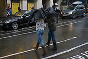 London, UK. Sunday 23rd August 2015. Heavy summer rain showers in the West End. People brave the wet weather armed with umbrellas and waterproof clothing. Jackets working to protect from the rain.