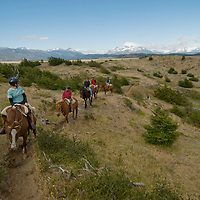 Adventure travelers ride horses in Torres del Paine National Park, Chile.