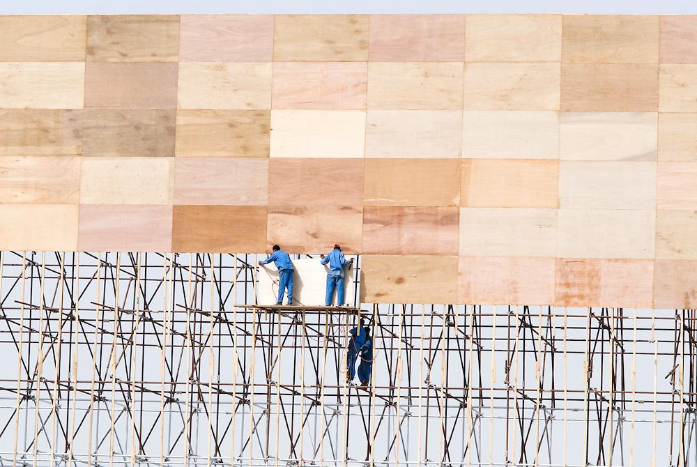 VAE,Dubai, Arbeiter bringen Holzplatten an einem Gerüst an. Es dient als Abschottung der Baustelle des Burj al Arab Towers während der Bauphase und wird zudem als Werbetafel genutzt. | UAE;  Dubai Workers attach wooden panels to a scaffolding. It is used to seal off the construction site of the Burj al Arab Tower during the construction phase and is also used as an advertising board