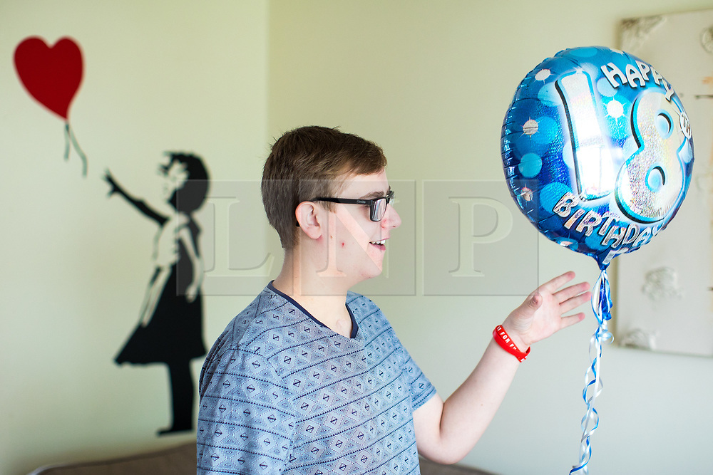 © Licensed to London News Pictures . 12/08/2017 . Manchester , UK . CONNOR SHAW (17 - turns 18 today - 13/08/2017) in his home ahead of his birthday . The Banksy stencil on the wall has significance as his parents say it represents the girl who died and whose heart Connor received in a life-saving heart transplant operation . When he was born doctors said he wouldn't live long due to a heart condition but he's doing well after receiving expert care , multiple operations and a heart transplant . His parents are campaigning for an opt-out organ donor register . See http://www.manchestereveningnews.co.uk/news/greater-manchester-news/never-thought-son-would-reach-13469965 for more information . Photo credit : Joel Goodman/LNP
