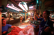 A stallholder of fresh fish and seafood weighs prawns on her scales in the covered Mercat lOlivar market, on 21st June 2001, in Palma, Mallorca, Balearic Islands, Spain.