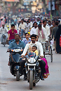 Family group on motorcycle in crowded street scene during holy Festival of Shivaratri in city of Varanasi, India