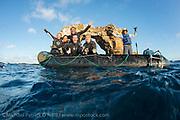 Scuba divers from the Galapagos Sky pose next to Darwins's Arch offshore Darwin Island, Galapagos, Ecuador.