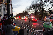 At 6:50am, police cars clear Central Park West, preparing for the Macy's Thanksgiving Day Parade. The sidewalks are already filled with people waiting for the parade, which starts at 9am.