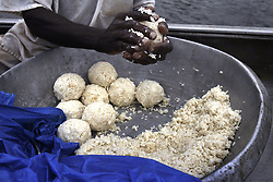 March 8, 2016 - Charlesville, Liberia - ANTHONY KPOH caregiver with Liberian Chimpanzee Rescue makes rice balls for chimps as they travel by boat to the islands on March 3, 2016.  LCR is a program of Humane Society of the United States.  HSUS and New York Blood Center came to an agreement recently in May 2017 after years of discussion about the care of research chimps NYBC had abandoned in Liberia, West Africa when they withdrew all funding for food and water.  In March 2016, a team from HSUS visits to view the situation.  NYBC also refused to pay for their caregivers who used their own meager finances to continue feeding them. They now live on six islands serving as a sanctuary.  The HSUS stepped in to assist and improve the dire situation in which the chimpanzees were literally left to die if not for the heroic efforts of their original caregivers who had worked for NYBC and were abandoned as well. (Credit Image: © Carol Guzy via ZUMA Wire)