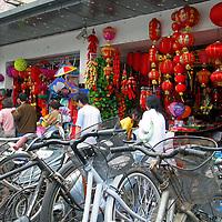 Asia, China; Shanghai. Bike racks and storefronts of a bustling Shanghai street.