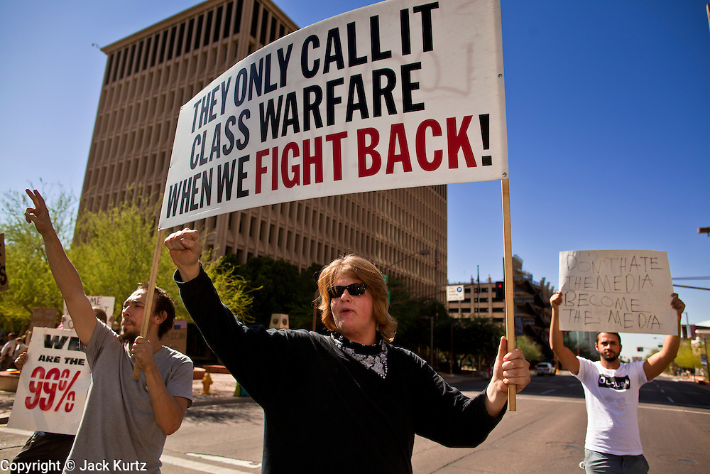 "22 OCTOBER 2011 - PHOENIX, AZ:    Occupy Phoenix protesters in the middle of a street in downtown Phoenix Saturday. The protesters stand in the street for as long as the Walk light is lit and then leave the street to avoid jay walking tickets. The demonstrations at Occupy Phoenix, AZ, entered their second week Saturday. About 50 people are staying in Cesar Chavez Plaza, in the heart of downtown. The crowd grows in the evening and on weekends. Protesters have coordinated their actions with police and have gotten permission from the city to set up shade shelters and sleep in the park, but without tents or sleeping bags, which is considered ""urban camping,"" instead protesters are sleeping on the sidewalk.      PHOTO BY JACK KURTZ"