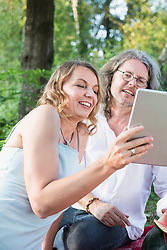 Couple on picnic using tablet, eating watermelon amidst nature, Bavaria, Germany