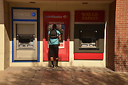 A young man uses an ATM on a college campus.