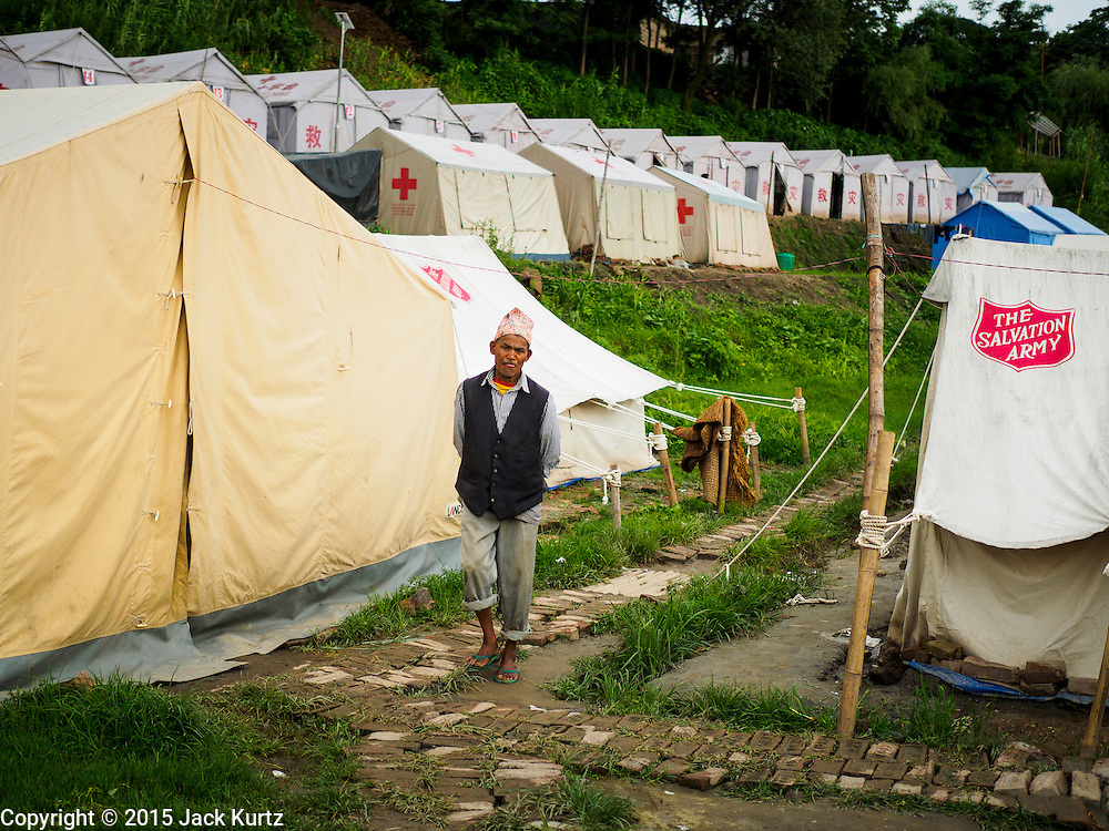 02 AUGUST 2015 - BHAKTAPUR, NEPAL:  A man walks through one of the larger Internal Displaced Persons (IDP) camps on the edge of Bhaktapur. The Nepal Earthquake on April 25, 2015, (also known as the Gorkha earthquake) killed more than 9,000 people and injured more than 23,000. It had a magnitude of 7.8. The epicenter was east of the district of Lamjung, and its hypocenter was at a depth of approximately 15km (9.3mi). It was the worst natural disaster to strike Nepal since the 1934 Nepal–Bihar earthquake. The earthquake triggered an avalanche on Mount Everest, killing at least 19. The earthquake also set off an avalanche in the Langtang valley, where 250 people were reported missing. Hundreds of thousands of people were made homeless with entire villages flattened across many districts of the country. Centuries-old buildings were destroyed at UNESCO World Heritage sites in the Kathmandu Valley, including some at the Kathmandu Durbar Square, the Patan Durbar Squar, the Bhaktapur Durbar Square, the Changu Narayan Temple and the Swayambhunath Stupa. Geophysicists and other experts had warned for decades that Nepal was vulnerable to a deadly earthquake, particularly because of its geology, urbanization, and architecture.      PHOTO BY JACK KURTZ