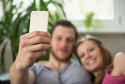 Couple taking selfie in living room and smiling, Munich, Bavaria, Germany