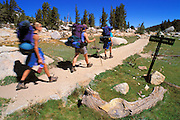 Family backpacking past a trail sign along Rafferty Creek in the Tuolumne Meadows area, Sierra Nevada Mountains, Yosemite National Park, California