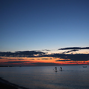 A view of the sunset from Galley Beach beachside restaurant, as paddle boarders paddle past. Nantucket,  Nantucket Island, Massachusetts, USA. Photo Tim Clayton
