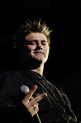 """Brian McFadden sticks two fingers up to the camera as Westlife play their third consecutive concert at the Hallam FM Arena at the start of their """"Unbreakable"""" Tour 2003 Monday 21st July 2003<br /> <br /> Image Copyright Paul David Drabble<br /> 21 July 2003"""