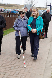 Visually impaired people with carers on outing to Denby Pottery. Woman with volunteer.