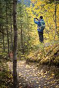 Woman taking pictures of fall colors, Denali National Park, Alaska