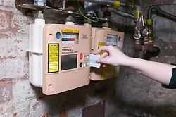 Woman swiping gas prepayment card through electronic token metre,