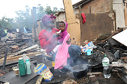 South Africa - Durban - 17 June 2020 - Xolile Ngubane from Malaca informal settlement feeding her baby Khethiwe Ngubane (1) a slice of bread whilst boiling water to make teain the open ground as their shack was burnt to ashes in the fire that ravaged the area last week<br /> Picture: Doctor Ngcobo/African News Agency(ANA)<br /> Picture: Doctor Ngcobo/African News Agency(ANA)