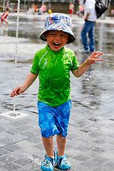 © Paul Thompson Licensed to London News Pictures. 26/07/2014. Bradford West Yorkshire. Nicholas Tidswell-Thompson, 3 years old enjoying the fountains in Bradford's Centenary Square. Photo credit : Paul Thompson/LNP