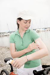 Mature woman taking care of her forearm, applying cosmetic cream, Bavaria, Germany