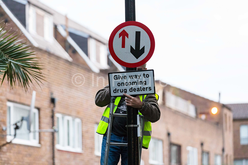Community activists from the 'Columbia Road Cartel' erect hoax 'Give way to oncoming drug dealers' road signs as part of the anti drugs street art campaign in residential streets near Columbia Road in Shoreditch east London on September 16, 2018 to highlight high levels of drug dealing in this part of Tower Hamlets, where the cheapest heroin in Europe can allegedly be purchased. The road signs and markings were commissioned by residents from the Weavers Community Action Group who claim that the police and Tower Hamlets Council are failing to address the growing drugs problem in the area.  (photo by Vickie Flores / In Pictures via Getty Images)