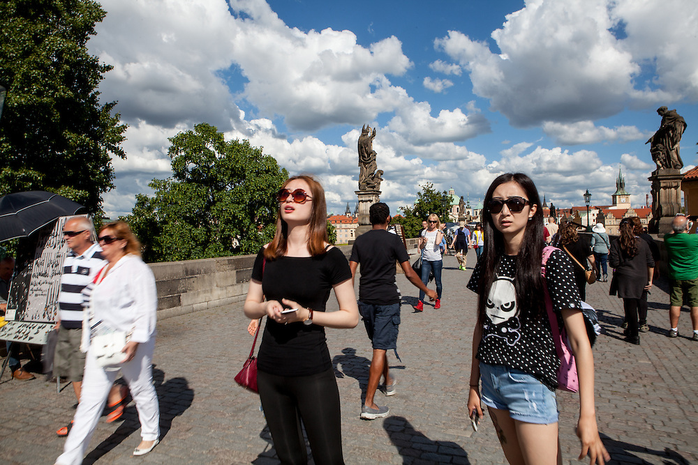 Two young women with sun glasses visiting Charles Bridge located in the city center of Prague. The Charles Bridge (Czech: Karlův most) is a famous historic bridge that crosses the Vltava river in Prague, Czech Republic and is probably the Nr.1 tourists magnet in the city.