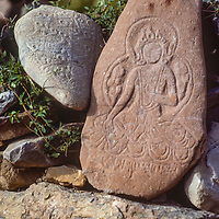 Carved Buddhist prayer stone of goddess near village of Kagbeni, Nepal