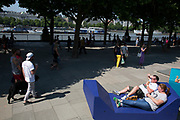 People relaxing on colourful metal benches situated along the South Bank in London, UK. Situated outside the National Theatre these structures provide a place for people to lie back and take the weight off their feet while people watching as others walk by. The South Bank is a significant arts and entertainment district, and home to an endless list of activities for Londoners, visitors and tourists alike.