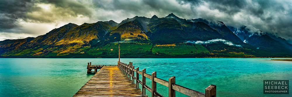 Inclement weather passes over at dusk, with a solitary lamp at the end of a jetty signifying hope in the face of adverse conditions.<br /> <br /> Queenstown Lakes, New Zealand<br /> <br /> Limited Edition Print; Edition of 125