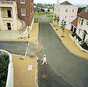 Seen from an aerial viewpoint which gives a perspective of deserted housing and empty roads, Jill Parmeter plays post woman. She is a resident of the experimental community village of Poundbury, Dorset, England. Delivering her own newsletter from door-to-door, she crosses Netherton Street and Tinten Lane to post her local news to residents and friends. The roads are empty of cars- nor is there anyone else to talk to. It is as if this community has vanished, leaving her alone. Poundbury is the visionary model village that Charles, Prince of Wales sought to develop in 1993 as a successful and pioneering town near Dorchester, built on land owned by his own Duchy of Cornwall, challenging otherwise poor post-war trends in town planning and to some extent following the New Urbanism concept from the US except that the design influences are European.