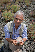 Giuseppe Mastrolorenzo, volcanologist with the Osservatorio Vesuviano and leading authority on local geology and civil evacuation plans, shows lava rock on the slopes of the dormant Vesuvius volcano, Italy.