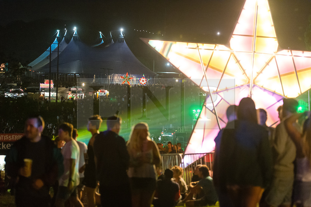 © Licensed to London News Pictures. 04/09/2014. Isle of Wight, UK. Festival goers enjoy the nighttime music and DJ's amongst a giant glitter ball and brightly lit stars at Bestival 2014 Day 1.  Bestival organisers claim the glitter ball to be the largest in the world and Guinness World Records officials will arrive to judge this.  Disco legend Chic (featuring Nile Rodgers) will be performing as Sunday night headliner to close the festival.   The weather has been warm and sunny. Photo credit : Richard Isaac/LNP