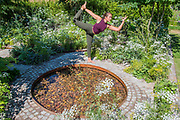 Lily Rodel practicing yoga on the Health & Wellbeing Lifestyle Garden designed by Alexandra Noble - Press day at The RHS Hampton Court Flower Show.