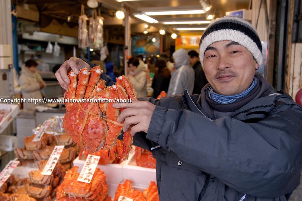 Stallholder displaying large red crab at fish market in Sapporo Hokkaido Island in Japan