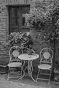 A white table and two chairs sit alongside a narrow street surrounded by plants and a sleeping cat creating a peaceful setting in Casole d' Else, Tuscany, Italy