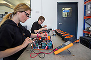 Technicians building new robots. Q-bot, underfloor insulation reducing carbon emissions potentially for 12 million households in the UK.   Q-Bot allows under-floor insulation to be installed at a much lower cost and without the disruption of existing methods by using a small robot that goes under the floor instead of having to take the floor up. © Andy Aitchison/ Ashden