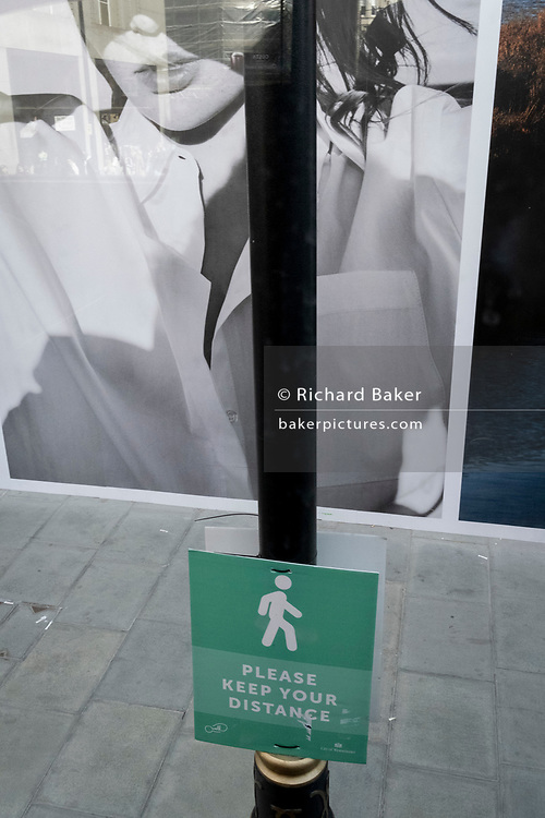 On the day that the UK government eased Covid restrictions to allow non-essential businesses such as shops, pubs, bars, gyms and hairdressers to re-open, a social distancing sign is beneath a large fashion ad on Oxford Street, on 12th April 2021, in London, England.