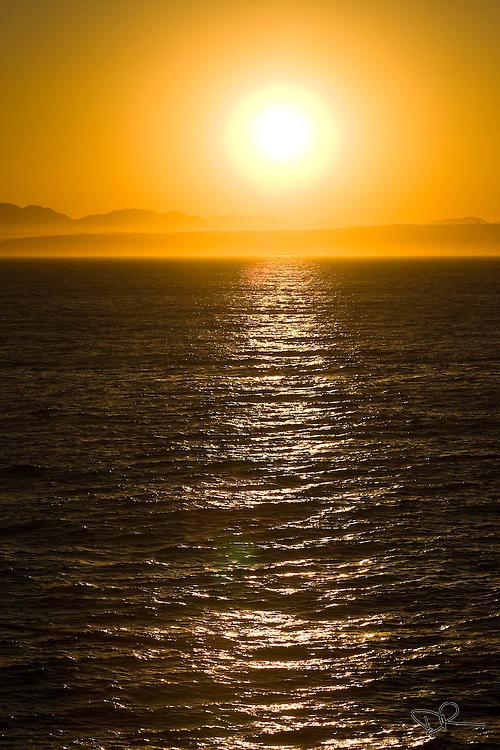 Sunrise at sea, with the coast of California on the horizon.