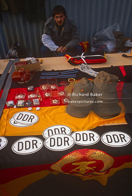Six months after the fall of the Berlin Wall, a young man sells memorabilia and merchandise from the former DDR (DGR) at a market stall near the Brandenburg Gate, on 1st June 1990, in Berlin, Germany.