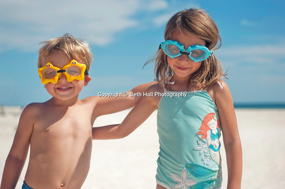 A 3-year-old boy and 4-year-old girl stand on the beach wearing starfish and dolphin shaped goggles in Fort Morgan, Alabama.