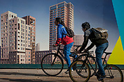 Cyclists pass a regeneration project hoarding at Elephant Park, Elephant & Castle, on 11th October 2016, in London, England. Southwark Council's development partner, Lendlease is regenerating over 28 acres across three sites at the heart of Elephant & Castle, in what is the latest major regeneration opportunity in zone 1 London. The vision for the £1.5 billion regeneration is to build on the area's strengths and vibrant character in order to re-establish Elephant & Castle as one of London's most flourishing urban quarters. The Elephant & Castle regeneration is of a scale rarely seen in central London and includes almost 3,000 new homes, plus office, retail, community, leisure and restaurant space.