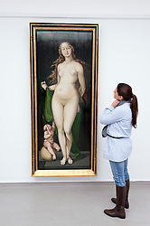 Woman looking at painting Venus and Cupid by Hans Baldung Grien in Kroller-Muller Museum in The Netherlands