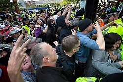 "© Licensed to London News Pictures . 22/08/2015 . Manchester , UK . Anti-fascists surge forwards as demonstrators are driven away on a coach . Far-right nationalist group , "" North West Infidels "" and Islamophobic , anti-Semitic and white supremacist supporters , hold a rally in Manchester City Centre . Photo credit : Joel Goodman/LNP"