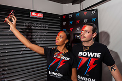 © Licensed to London News Pictures. 25/10/2021. LONDON, UK.  Store staff take a selfie at the opening of a David Bowie pop-up shop in Heddon Street in the West End.  Open 75 days before the late singer's 75th birthday, the pop-up is located close to where Bowie posed as Ziggy Stardust on the cover of his 1972 album The Rise and Fall of Ziggy Stardust and the Spider from Mars.  The store sells limited edition records and memorabilia curated by his estate and will be open until January 2022. A sister shop will open in New York and both form part of a year long celebration of David Bowie's 75th birthday.  Photo credit: Stephen Chung/LNP