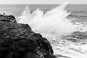 A wave crashes into the rocks at Kirkjufjara beach in southern Iceland, as a tourist looks on