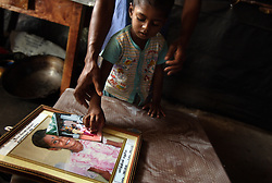 Vithusan Partheepan looks at a photograph of his deceased sister, Madusia, inside their temporary home, Batticaloa, Sri Lanka, July 8, 2005. The Partheepan family first took refuge in the Anapandi Hindu temple after their house was flattened in the tsunami. They were then moved to the Hindu college and placed in tents donated by aid organizations. Six months later, they were still living on the land where their tents were set up, but they also had a partition of their own in a tin hut with a thatched roof. With earned and borrowed money, plus a little given to them for the loss of Madusia, the family bought a small piece of land, where they plan to start anew.