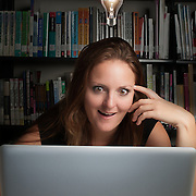 Woman in library working on computer with bright idea light bulb over her head.  Model Release # ER20120624-00003
