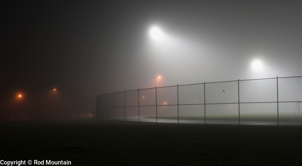 Night fog fills the empty track and soccer field. Burnaby, British Columbia