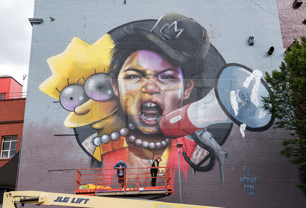© Licensed to London News Pictures.  28/07/2018; Bristol, UK. Work in progress at Upfest, The Urban Paint Festival, 2018 with themes this year including the Simpsons cartoon series and 100 years of the first women getting the vote. NOMAD CLAN are pictured working on their giant mural with the character of Lisa Simpson on the side of the Tobacco Factory in Bedminster, Bristol. Nomad Clan is possibly the biggest female duo in world street art, having completed the largest mural in the country back in 2017. Their challenge this year is a unique one; to celebrate the suffrage movement with a tie in to The Simpsons using the show's titular post-modern feminist, Lisa Simpson. Upfest which is Europe's largest Street Art and Graffiti Festival takes place in the Bedminster area of Bristol between Saturday the 28th and Monday 30th of July. In celebration of their 10th anniversary, Upfest will feature the animated family, The Simpsons with 2018 festival goers treated to artist interpretations including Homer, Marge, Bart, Lisa, and Maggie. The festival has also teamed up with Bristol Women's Voice to celebrate the centenary of the first votes for women, and together Upfest and Bristol Women's Voice will celebrate the progress made since 1918, with three artists including Nomad Clan chosen to portray the suffrage movement and the rights of women. Upfest will have 400 artists from 70 countries in attendance, including this year's lead artists Insane51, L7m, London Police, Nomad Clan, Odeith, and Paris. This year, three Upfest artists have been selected by The Simpsons creator Matt Groening to bring The Simpsons to life in their own unique styles: Bao, born and based in Hong Kong, is known for her freestyle work with vibrant murals and illustrations; Soker, a wildstyle writer, is one of Bristol's finest talents and has been putting his mark on the city since the late 80's; Nomad Clan, the collective of Cbloxx and AYLO, one of the most sought-after duos in the international globa